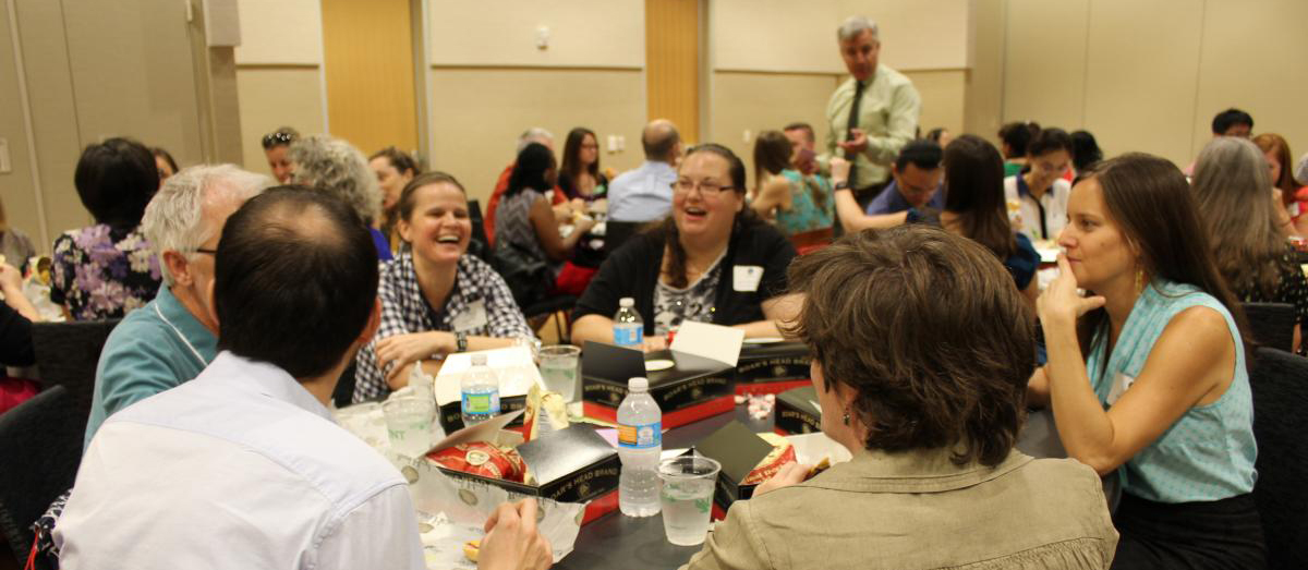 Photograph of faculty chatting at lunch tables with Mike McPherson standing in the crowded room.