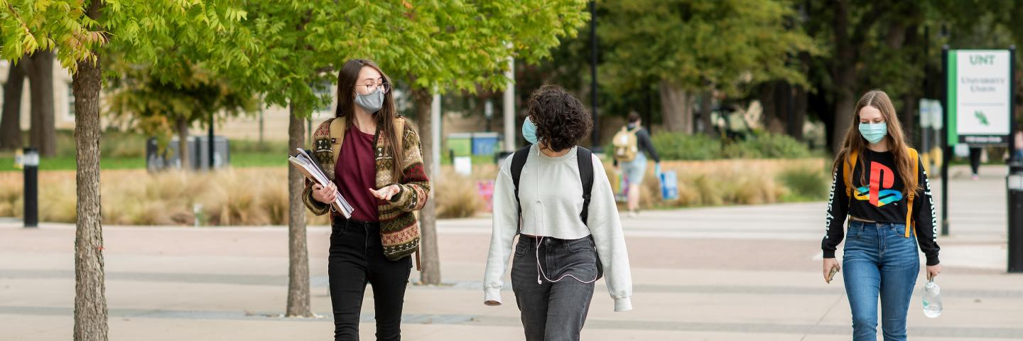 Students wearing masks walking on the UNT campus.